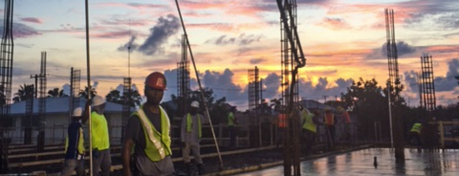 Crew stands at a concrete pouring area with pipes and wet concrete visible
