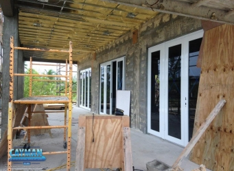 Scaffolding and wooden boards are seen on the outside deck while spray foam insulation is installed on the ceiling.