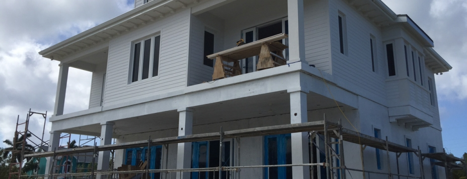 Right angle of the house with scaffolding visible and right side windows in sight.