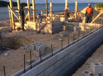Construction of the concrete shell continues as crews place and secure blocks over the rebar supports. Cayman Structural Group is responsible for the foundation and shell construction and are the structural contractors for this luxury custom home.
