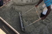 A construction worker spreads concrete to create a smooth, level floor as he works to complete the foundation and concrete shell of this custom luxury home.
