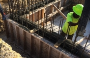 A construction worker pours concrete into molds, creating walls for the luxury home project. Cayman Structural Group is the structural contractor for this site, building the concrete foundation and shell.