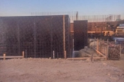 Rebar is placed around molds before concrete is poured to form the walls of the luxury custom home.