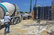 Workers pump concrete between molds to create a wall during construction.