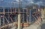 Workers place molds over rebar supports in preparation to pour concrete to build the walls of this custom home.