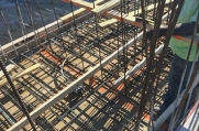 A worker adjusts a rebar support before additional concrete is poured.