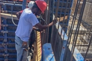 Workers carefully position rebar supports and wooden molds in preparation to pour additional concrete to create the walls of this home.