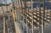 Rebar supports shoot out of a wall as workers prepare to begin constructing the second floor of this massive luxury home.