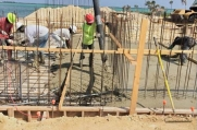 Crews pump concrete as they finish work on the concrete foundation of the luxury custom home.
