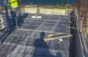 A construction worker assembles a sub-floor onto which wooden molds and rebar will be installed before concrete is poured to create the floor.