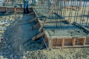 Strip footing is poured before the concrete walls of the luxury home are built.