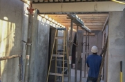 A worker stands below the suspended slab as construction continues on this luxury home in West Bay.