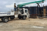 Concrete is pumped from a truck to build walls and floors for this luxury home.
