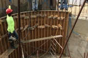 Construction workers inspect this custom curved concrete wall as they begin to remove its wooden molds.