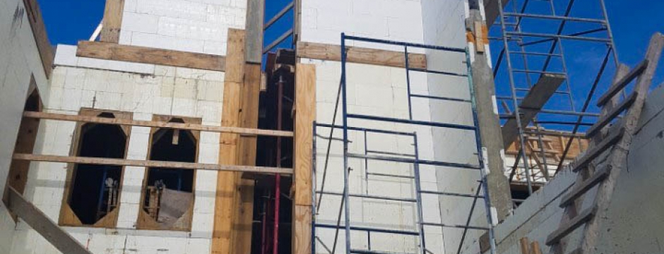 A side view of the house shows the walls are being finished off in certain areas.