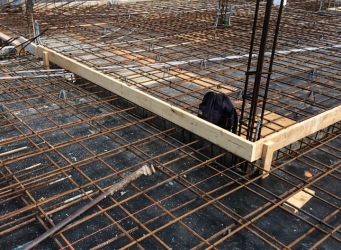 Rebar exposed on the roof of the structure as workers bend it into place.