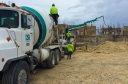 Concete truck pumps concrete on the site to a location where it is needed.