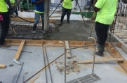 Four workers adjust pipes and rebar on top of the ceiling.
