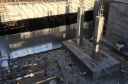 Rebar handing over the exposed foundation of a lower level.