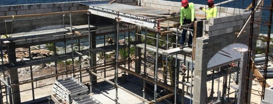 Three workers hand concrete and boards to one another along scaffolding.