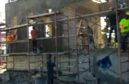Many workers smooth concrete on the exterior of the building.