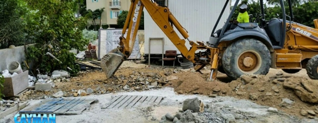 Back hoe leveling up and cleaning site.
