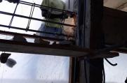 A crew member cuts rebar on some scaffolding.
