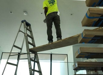 A crew member accesses the second floor stairs to apply coating.