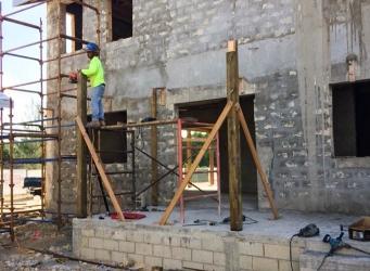 Crew member climbs scaffolding.