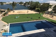 Rolling the turf in place between the pool and the beach.