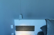 A modern light fixture is installed in the master bedroom.