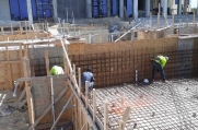 Workers ensure the rebar is flush against the pool frame.