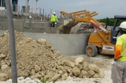 A front loader dumps fill into the newly formed concrete walls to make the deck around the pool.
